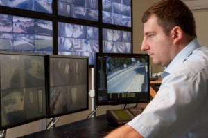 Man monitoring cctv cameras in modern control room