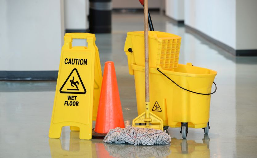 Caution sign with mop and bucket on a floor