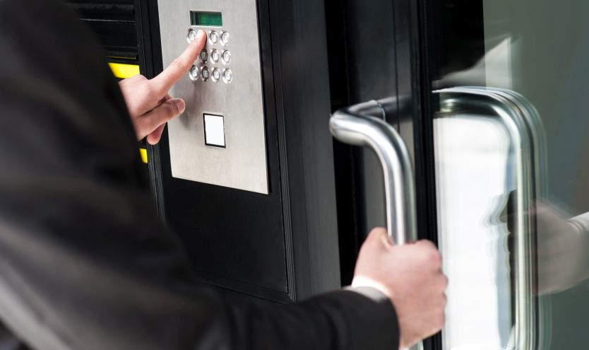 A man entering a code into an access control system