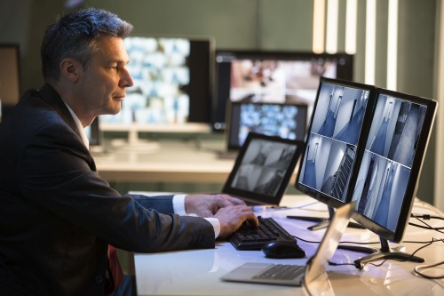 man at a desk watching surveillance footage