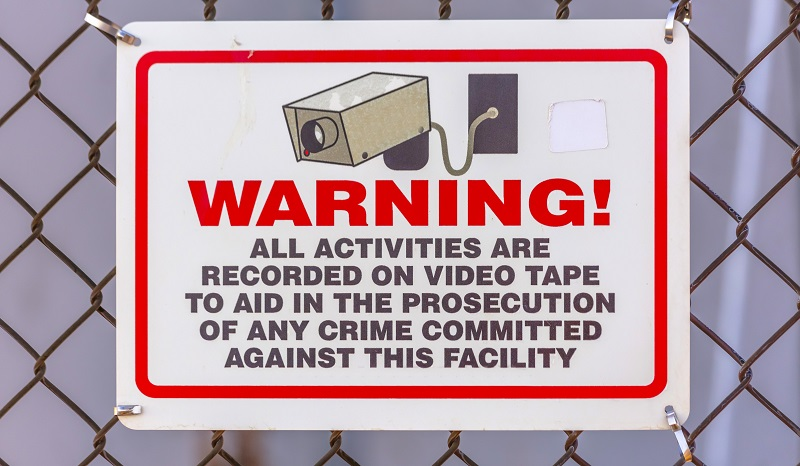 The sign says all activities are recorded on video tape to aid in the prosecution of any crime committed against this facility.
