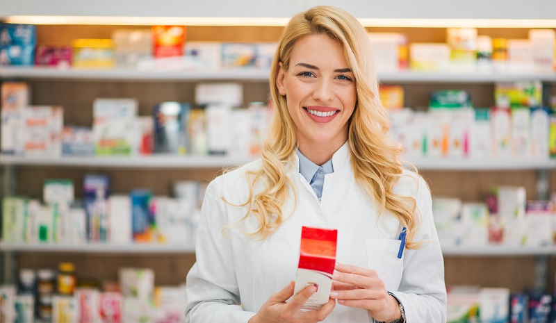 Smiling pharmacist holding medication, looking at camera.